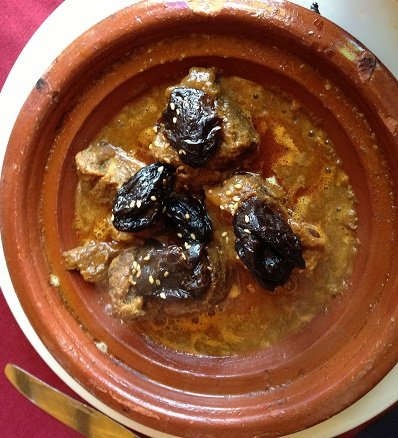 Steaming hot tajine with meat and dates.