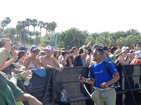 Festival worker spraying the hot crowd with water.